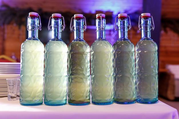 Ряд бутылок самодельного алкоголя.