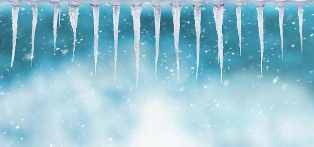 Ряд сосулек на размытом фоне во время снегопада