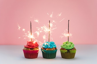 Row of illuminated firework over the cupcakes against pink backdrop
