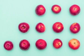 Row of increasing red apples against blue background