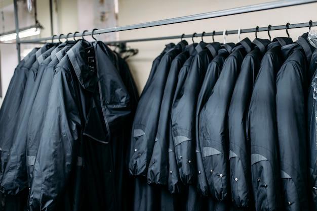 ハンガー、衣料品店、縫製工場、またはドレス生地のジャケットの列。ラックの服