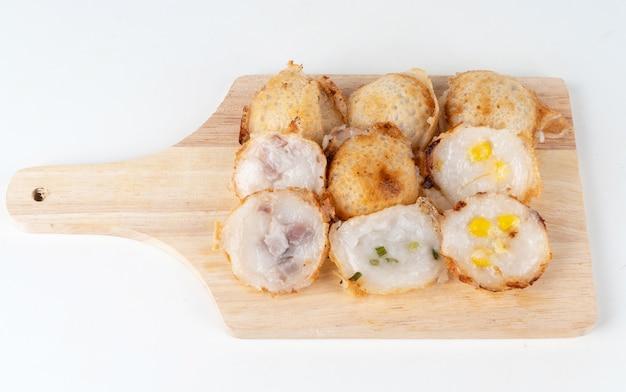 Ряд вида тайских конфет с кукурузным таро и кориандром на разделочной доске.