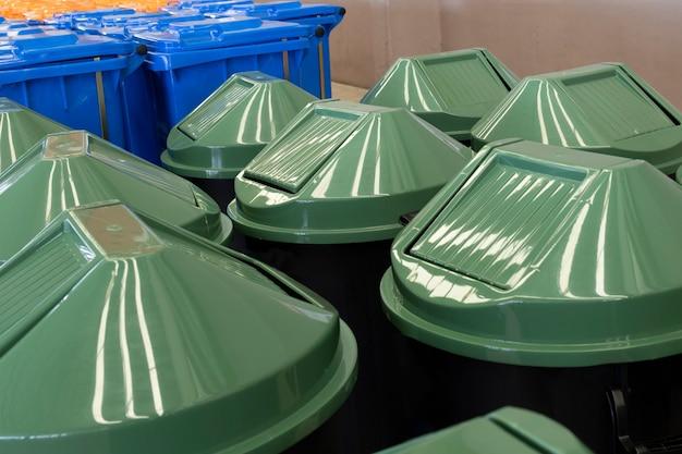 Ряд больших темно-зеленых промышленных пластиковых контейнеров для мусора.