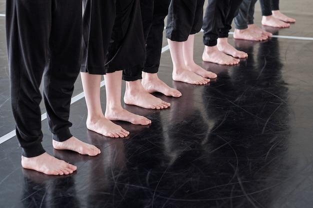 レッスンで運動しながらダンススタジオの床に立っている黒いズボンの裸足の若いダンサーの足の列