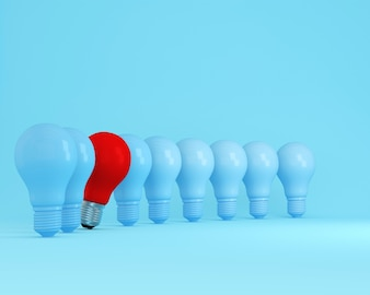Row of light bulbs red one different idea on light blue background