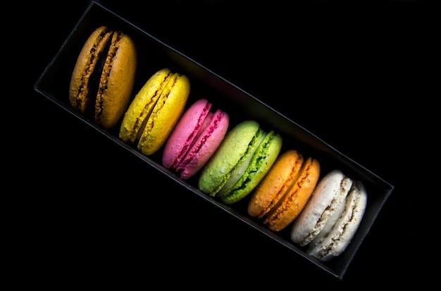 マカロンクッキーの虹色の行。黒い背景に対角線の黒い箱のビスケット。
