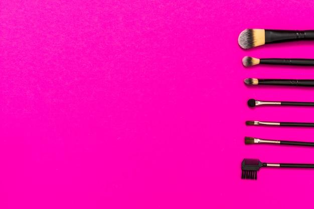 분홍색 배경에 텍스트를 작성하기위한 복사 공간 메이크업 브러쉬의 행