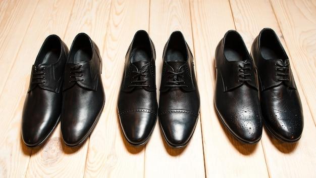 Ряд мужской кожаной обуви на деревянном полу