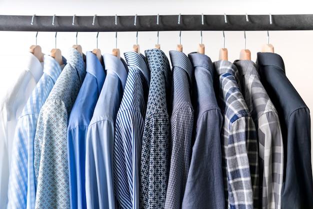 Ряд мужских рубашек в синих тонах на вешалке