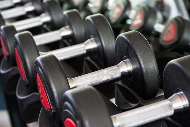 ウェイト トレーニング用のスポーツ クラブのラックに金属ダンベルの列
