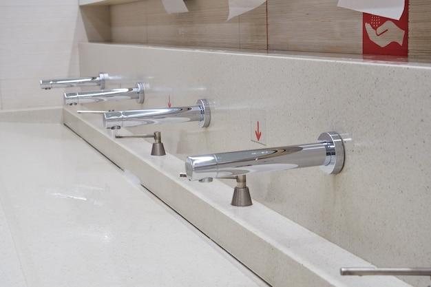 공중 화장실, 레스토랑, 호텔, 쇼핑몰에 현대적인 흰색 세라믹 세면대가 줄지어 있습니다.