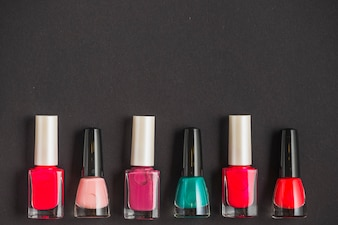 Row of multi colored nail varnish bottles on black background