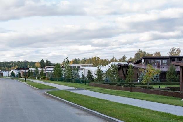 푸른 잔디와 도로가 앞에 있는 나무 사이에 서 있는 시골 환경의 새로운 현대적인 시골집이나 코티지가 줄지어 서 있습니다.