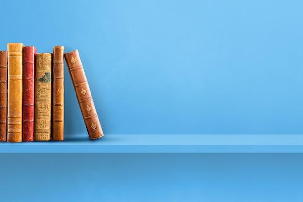 Строка старых книг на синей полке. горизонтальная фоновая сцена
