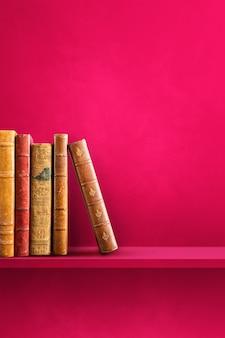 Строка старых книг на розовой полке. вертикальная фоновая сцена