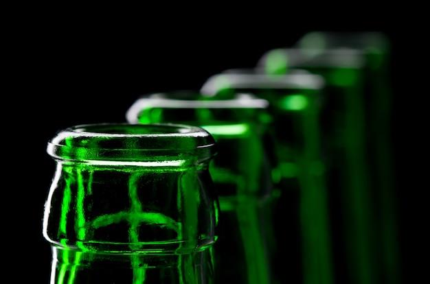 開いた緑のビール瓶の列。クローズアップビュー