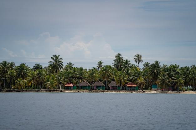 Ряд пальм и крошечных бунгало на маленьком острове в море приключений, отпусков и путешествий ...