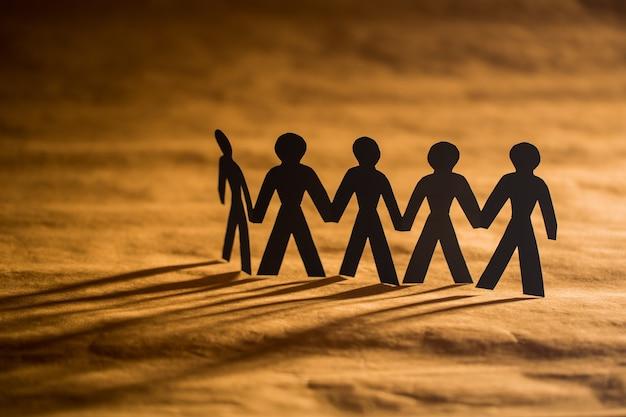 Строка бумажных людей, отбрасывающих длинные тени на коричневый фон