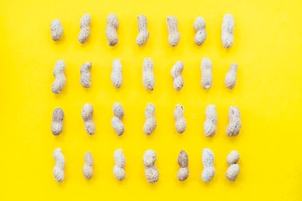 Row of peanuts shell on yellow background