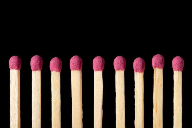 黒のクローズアップにピンクのマッチの列