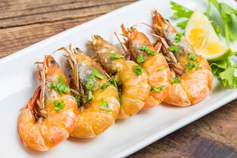 Row of prawns decorated with herbs