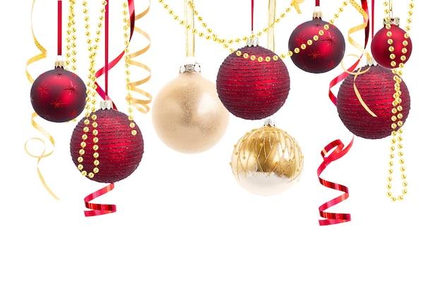 Ряд красных и золотых новогодних шаров с вьющейся бумагой, изолированные на белом фоне