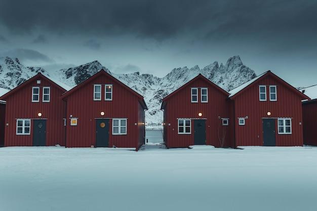 노르웨이 사크리소이 섬의 눈 덮인 해안에 줄지어 있는 빨간 오두막