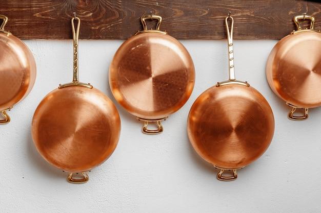 木の板に掛けられたさまざまなサイズの光沢のあるきれいな銅鍋の列