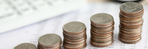 Ряд серебряных монет, стоящих на финансовый отчет бумаги крупным планом