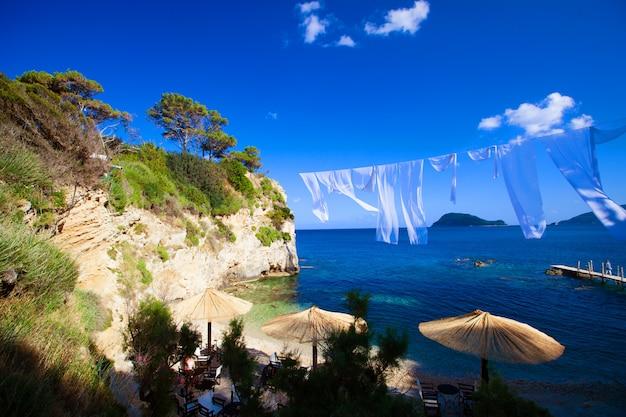 해변에서 밀 짚 우산과 라운지의 행