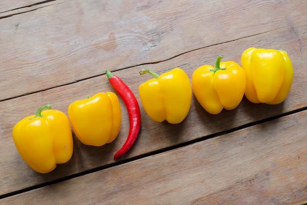 ヴィンテージの木製テーブルの上に甘い黄色のパプリカとそれらの間に1つの赤唐辛子の列