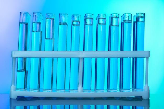 Ряд пробирок с жидкостями на синем и зеленом фоне тонированное