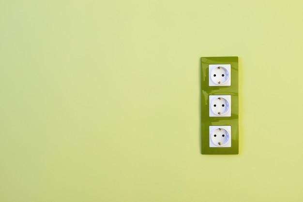 Ряд трех вертикальных европейских белых электрических розеток на зеленой стене