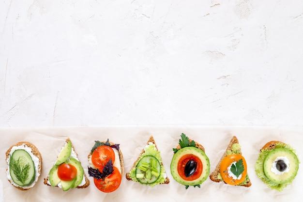 Ряд вегетарианские бутерброды на белом фоне.