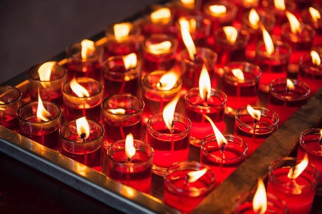 중국 사원에서 유리에 불꽃 봉헌 종교 붉은 촛불의 행