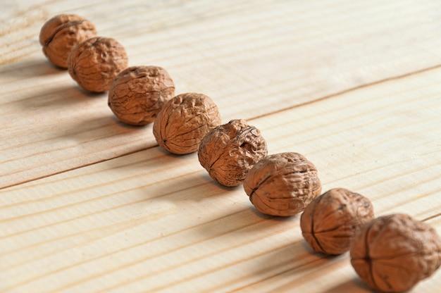 Ряд грецких орехов на деревянном столе, акцент делается на грецкие орехи в центре