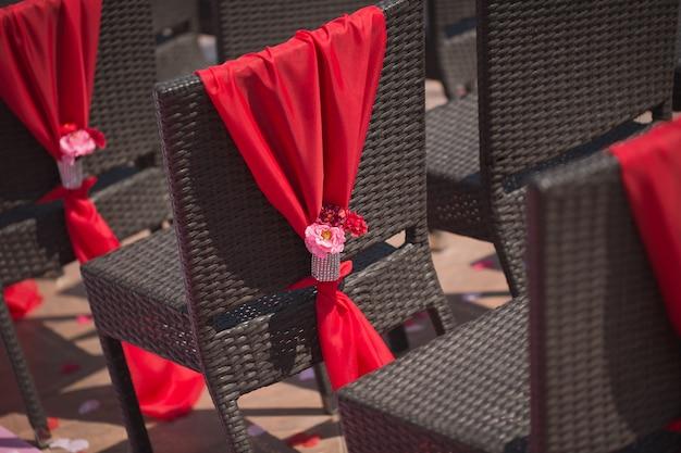 Ряд свадебных стульев, украшенных красными розами