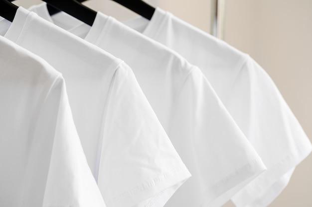 Ряд белых футболок на вешалках, висящих на стойке