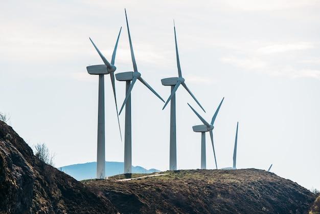 Ряд ветряных мельниц, вырабатывающих возобновляемую энергию, расположен в травянистой местности на фоне облачного неба