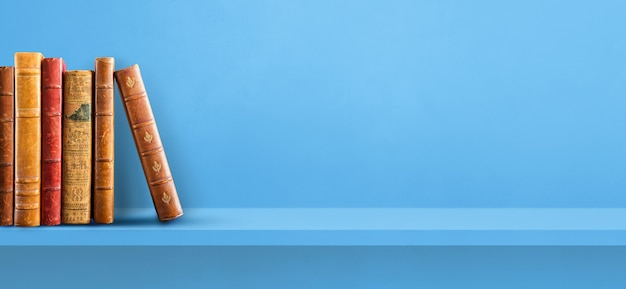 Row of old books on blue shelf. horizontal background banner