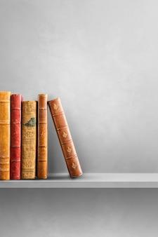 Row of old books on grey shelf. vertical background scene