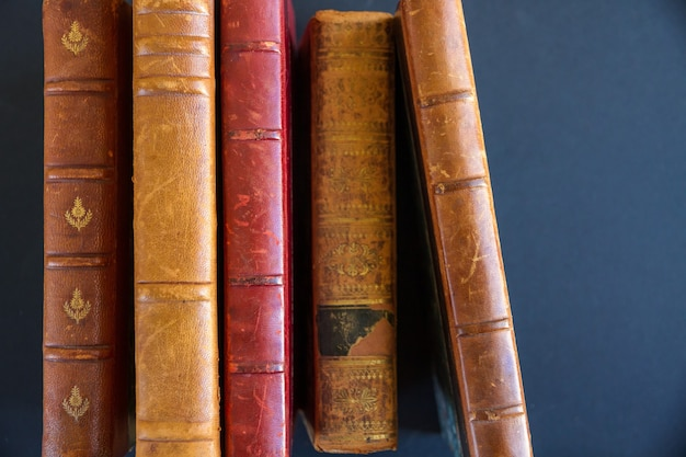 Row of old books isolated on dark background