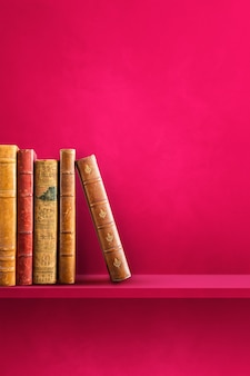 Row of old books on pink shelf. vertical background scene