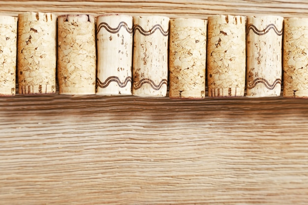 A row of old wine corks on a wooden background.