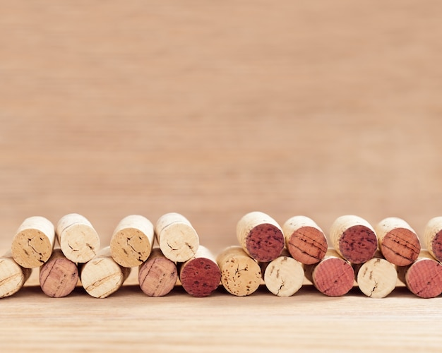 A row of old wine corks on a wooden blurred background with copy space.