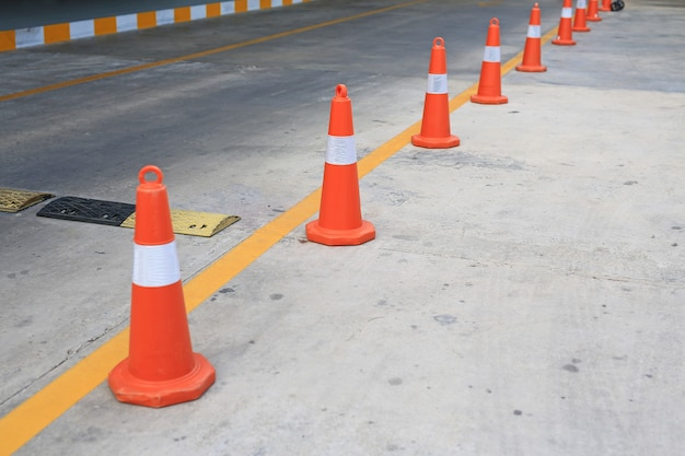 Row of orange rubber traffic cone placed in road.