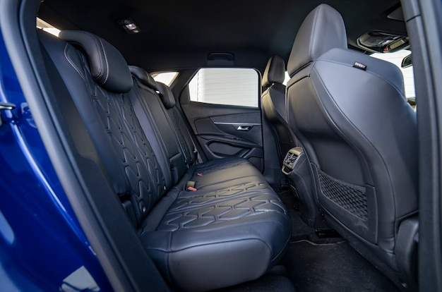 Row of passenger rear seats upholstered in black dry-cleaned fabric; pre-sale preparation blue car