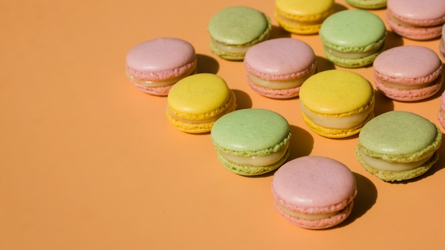 Row of pink; green and yellow macaroons on beige backdrop