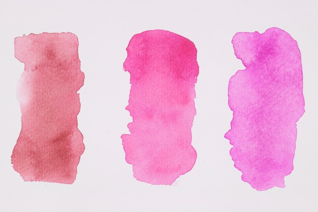 Row of pink and red paints on white paper