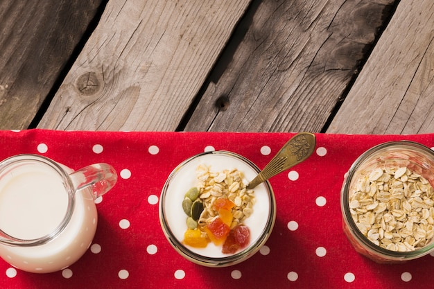 Row of pitcher, yogurt and muesli jar on red napkin over the wooden table